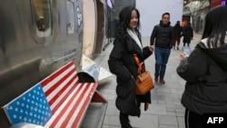 中国购物者在北京一个热门购物中心,长凳上画着美国国旗。(2019年1月6日)
