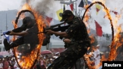 FILE - Chinese People's Liberation Army (PLA) soldiers jump through rings of fire in a war game as part of the show for the public during an open day at the Ngong Shuen Chau Naval Base on Hong Kong's Stonecutters Island, July 28, 2012.