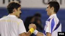 Petenis Swiss Roger Federer mengucapkan selamat kepada petenis Serbia Novak Djokovic setelah memenangkan partai semifinal Australia Terbuka hari Kamis (27/1).