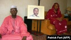 La femme de l'opposant disparu Ibni Oumar Mahamat Saleh, Sadia Brahim, à droite, et son cousin Moussa Mahamat Saleh posent devant le portrait du leader de l'opposition chez lui à N'Djamena, le 15 mai 2008.