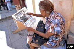 A woman reads 'Tribuna de la Habana' newspaper in central Havana a day before the visit of Pope Francis to Cuba on Sept. 18, 2015.