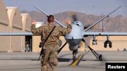 سرباز امریکایی در حال رهنمایی طیارۀ بی پیلوت امریکایی در میدان هوایی کندهار