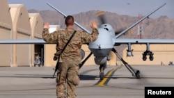"""2016年3月9日一名美军空军士兵在坎大哈机场导引一架美国空军MQ-9""""收割者""""无人机滑向跑道"""
