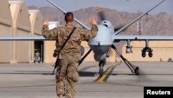 یک سباز آمریکایی درحال هدایت یک پهپاد آمریکایی در افغانستان.