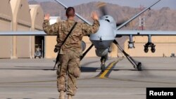 A U.S. airman guides a U.S. Air Force MQ-9 Reaper drone as it taxis to the runway at Kandahar Airfield, Afghanistan, March 9, 2016.