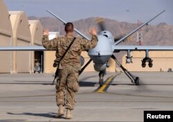 A FILE - US airman guides a US Air Force MQ-9 Reaper drone as it taxis to the runway at Kandahar Airfield, Afghanistan.