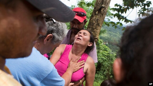 Margarita Mendez is helped by friends while she waits for news of her son Salvador Urbina, one of the miners trapped at El Comal gold and silver mine in Bonanza, Nicaragua, Aug. 29, 2014.