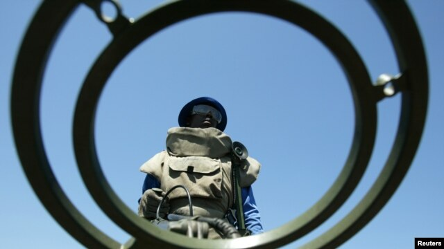 FILE - An anti-personnel mine detecting worker stands at a mine field near Vilancoulos in southern Mozambique, 450 km (265 miles) north east of Maputo, Nov. 2004 file photo.