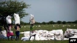 Des femmes portent des sacs de nourriture distribués par Oxfam à Padding, dans le Soudan du Sud, le 3 juillet 2017.