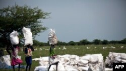 Wanawake wakibeba magunia ya nafaka yaliyo dondoshwa kwa ndege na Shirika la Chakula Duniani (WFP) ambayo yanasambazwa na shirika lisilo la kiserikali la Oxfam Julai 3, 2017 Sudan Kusini.