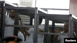 FILE - Mohamed Fahmy (R) and other defendants react at a court proceeding in Cairo, June 23, 2014.