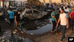 People gather at the scene of a deadly car bombing in the Habibiya neighborhood of Sadr City, Baghdad, Iraq, Aug. 15, 2015.
