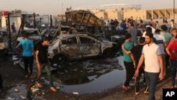Orang-orang berkumpul di lokasi bom mobil di daerah Habibiya, Sadr City, Baghdad, Irak, 15 Agustus 2015.