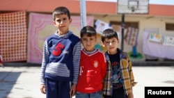 Displaced Iraqi boys pose at the Bilad al-Arab Elementary School, which has been turned into a housing complex for almost 31 families who fled Mosul because of Islamic State violence, in Baghdad, Oct. 22, 2014.