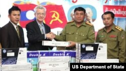 Mr. Lacy Wright, Director of the Law Enforcement and Narcotics Section at the U.S. Embassy gives office supplies to Colonel Khamphonh Sihapanya, Director of the Lao Drug Police.