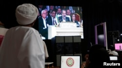 Members of the media watch Syrian National Coalition (SNC) President Mouaz al-Khatib during a live address during the opening of the Arab League summit in Doha, Mar. 26, 2013.