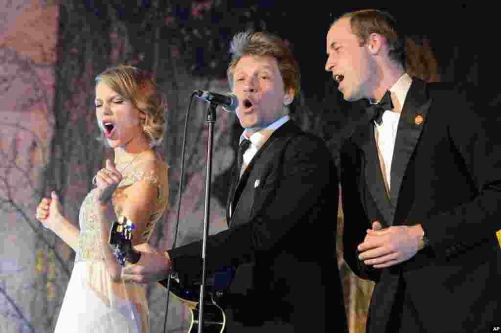 Britain's Prince William, the Duke of Cambridge, right, sings with U.S. singers Taylor Swift, left, and Jon Bon Jovi at the Centrepoint Gala Dinner at Kensington Palace in London, Nov. 26, 2013. Centrepoint is a charity supporting homeless young people aged 16-25 and the Duke is patron of the organisation.