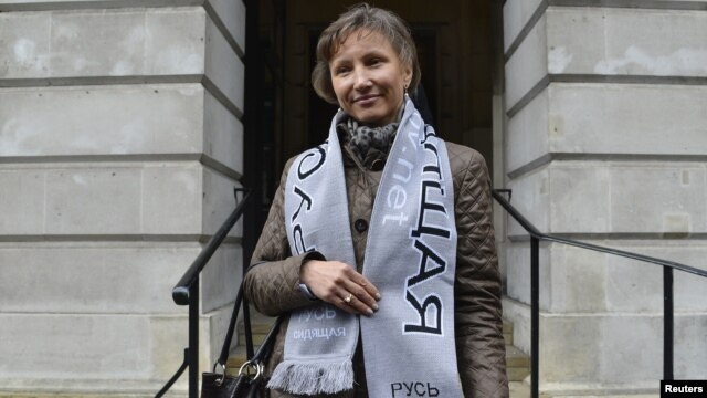Marina Litvinenko wears a scarf in support of jailed Russian political prisoners, as she leaves a hearing into the death of her husband, Alexander Litvinenko, in London, November 2, 2012.