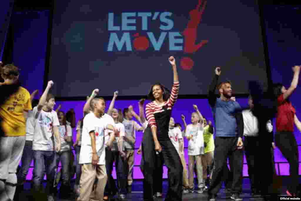 """La primera dama Michelle Obama participa de la danza """"Interlude"""" con estudiantes en el estadio Wells Fargo en Des Moines, Iowa, como parte del aniversario del programa """"A Moverse"""" (""""Let's Move!""""). (Official White House"""