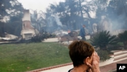加州范杜拉市一名妇女在被烧毁的家前掩面哭泣。(2017年12月5日)