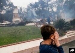 Žena plače i sakriva lice u blizini svoje uništene kuće, nakon što je požar zahvatio Venturu, Kalirofnija, 5. decembra 2017.
