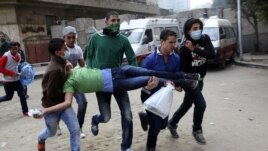 Egyptians carry a protester wounded in clashes with security forces near Tahrir square, where an opposition rally has been called for to voice rejection of President Morsi's seizure of near absolute powers in Cairo, Egypt, November 27, 2012.