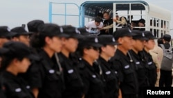 FILE - The Chinese police SWAT team lines up as suspects of telecom fraud arrive before their deportation to China at the International Airport of Phnom Penh, Cambodia June 24, 2016.