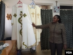 Sarah Ndungu, secretary and accountant for the Dolly Craft Sewing Project in Kangemi slum, Nairobi, shows the two chasubles her group designed and constructed for Pope Francis during his visit to Kenya later this month, Nov. 12, 2015. (Photo: J. Craig / VOA)