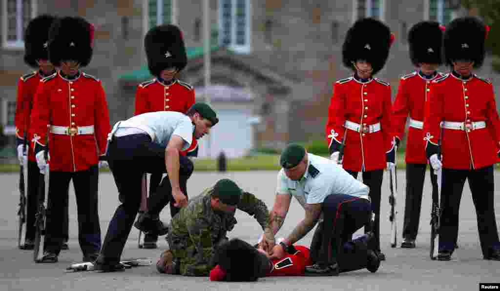 A member of the honor guard is attended to by colleagues after fainting prior to Mexican President Enrique Pena Nieto's inspection at the Citadelle in Quebec City, Canada, June 27, 2016.