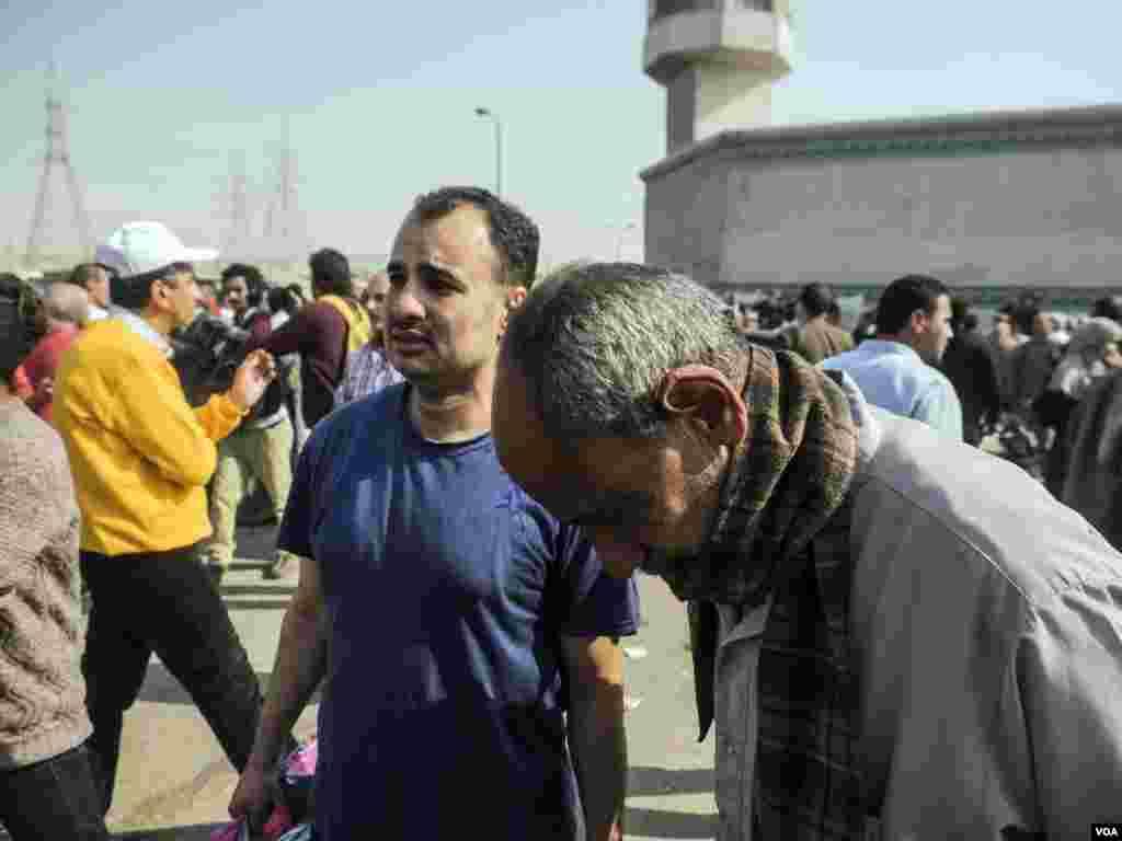 """Yasser Awad (berkaos warna biru) menangis bersama ayahnya setelah dibebaskan dari penjara Tora di Kairo. """"Masih ada tiga saudara laki-laki saya di penjara,"""" ujarnya (14/3). (VOA/H. Elrasam)"""
