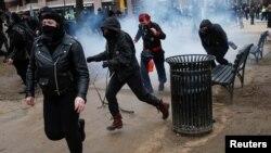Activistas anti-Trump corren luego que la policía les lanzó granadas de aturdimiento para combatir los destrozos que estaban perpetrando en el centro de Washington antes de la toma de posesión de Donald Trump.