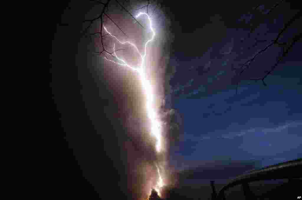Lightning flashes as Taal Volcano erupts,Jan. 12, 2020, in Tagaytay, Cavite province, outside Manila, Philippines. A tiny volcano near the Philippine capital that draws many tourists for its picturesque setting in a lake belched steam, ash and rocks in a huge plume, prompting thousands of residents to flee and officials to temporarily suspend flights.