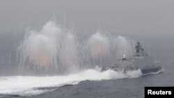 FILE - Flares are set off from a Taiwan navy missile ship in a military drill outside a naval base in Kaohsiung port, southern Taiwan, Jan. 27, 2016.