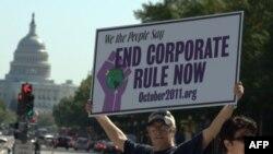 На плакате написано: «Мы, американский народ, говорим: остановите власть корпораций»
