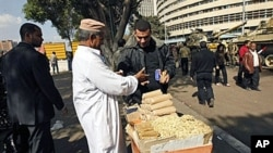 An Egyptian man sells popcorn to people walking outside the national TV building in Cairo three days after Egyptian President Hosni Mubarak stepped down, February 14, 2011