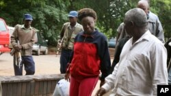 FILE: Zimbabwean human rights activist, Jestina Mukoko, center, is led into court in Harare, Zimbabwe Wednesday, Dec. 24, 2008. State media report that Mukoko, who went missing three weeks ago, is accused of attempting to recruit government opponents for military training to overthrow President Robert Mugabe. (AP Photo)