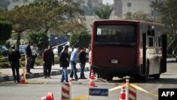 Egyptian security officials inspect the wreckage of a bus that was damaged by an explosion in Cairo, Dec. 26, 2013.