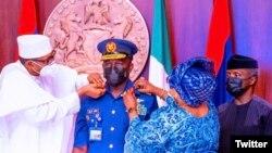 Buhari yana sakawa shugaban hafsan sojin sama aninai (Hoto: Twitter Nigerian Air Force)