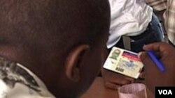 Foto achiv -Yon nonm kap egzaminen yon kat idantifikasyon elektoral