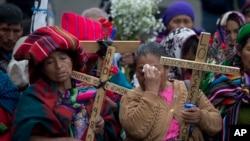 ARCHIVO - Mujeres indígenas rezan sosteniendo cruces de madera durante una ceremonia en honor de activistas de derechos humanos frente a la Corte Suprema en Ciudad de Guatemala. Feb. 25, 2016.