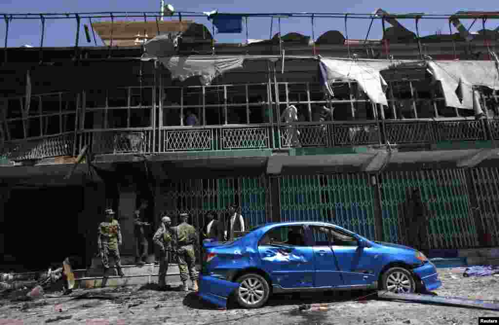 Afghan police guard at the site of a suicide attack in Kabul, May 16, 2013.