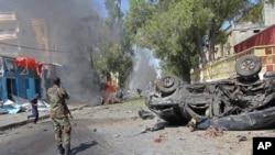 Un soldat somalien se tient près de l'épave d'une voiture en feu, après une explosion, à Mogadiscio, Somalie, 1 octobre 2016.