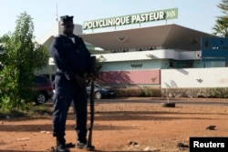 A police officer stands guard outside the quarantined Pasteur Clinic in Bamako, Mali on Nov. 12, 2014.