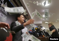 An unidentified person throws pieces of paper, resembling banknotes, as Russian opposition figure Ilya Yashin (L) presents his report in Moscow, Feb. 23, 2016.
