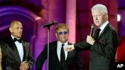 """Mantan Presiden AS Bill Clinton (kanan) memberikan sambutan di acara penggalangan dana untuk AIDS """"Life Ball"""", didampingi penyelenggara acara - Gery Keszler (kiri), dan musisi Inggris Elton John selaku penggagas acara tahunan ini di Wina, Austria (25/5)."""