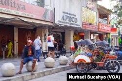 Tukang becak menanti penumpang di depan toko-toko yang tutup di Malioboro, Yogyakarta. (Foto: VOA/Nurhadi)