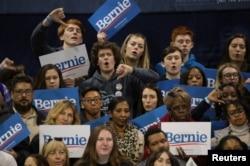 Los partidarios del aspirante presidencial demócrata de EE.UU., senador Bernie Sanders, reaccionan a sus felicitaciones por el candidato rival Joe Biden mientras Sanders habla en su mitin nocturno primario en Carolina del Sur en Virginia Beach, Virginia, el 29 de febrero de 2020.
