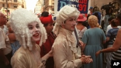 Oo la la! Three members of Le Studio Dramatique, a French acting group, participate in Bastille Day celebrations on 60th Street in New York City in 1997. (AP Photo/Suzanne Plunkett)