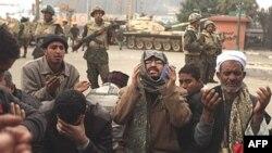 Người biểu tình chống chính phủ và các thành viên của nhóm Huynh Đệ Hồi giáo cầu nguyện phía trước các binh sĩ Ai Cập tại Quảng trường Tahrir ở Cairo