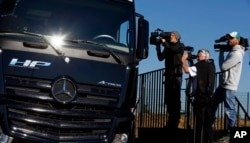FILE - TV crews film the Actros autonomous truck by Mercedes-Benz near Stuttgart, Germany, Oct. 2, 2015.